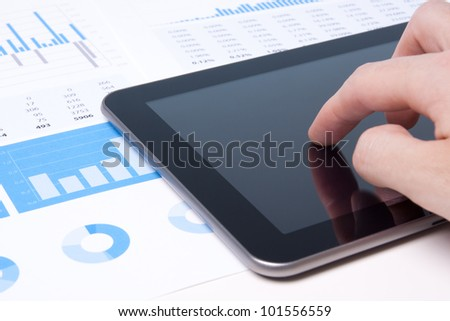 Modern business analyst working with digital tablet computer, sheet and graphs.