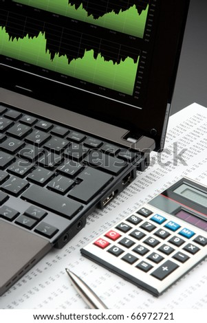 Modern business and stock market analyze with laptop, calculator, pen and printed data sheet