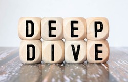 Modern business buzzword - deep dive. Top view on wooden table with blocks. Top view. Close up.
