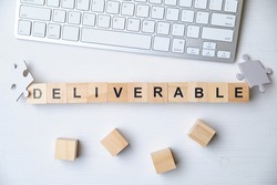 Modern business buzzword - deliverable. Top view on keyboard and puzzle with wooden blocks. Close up. Top view.