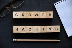 Modern business buzzword - growth hacking. Top view on wooden table with blocks. Top view. Close up.