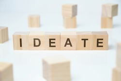 Modern business buzzword - ideate. Word on wooden blocks on a white background. Close up.