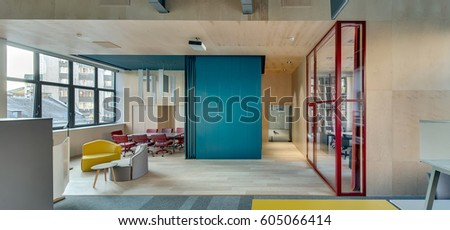 Modern business interior with wooden walls. There is a red glass wall with a door to the next room, big blue locker, zone with small sofas and round table, zone with long dark table and red chairs.
