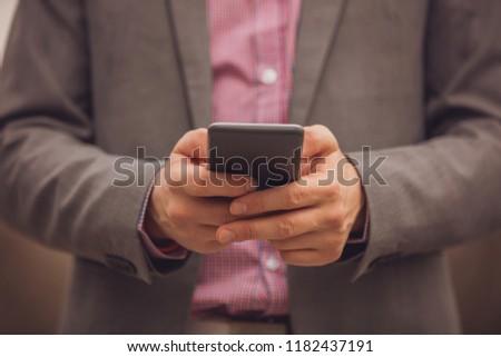 Modern business man using cellphone outdoors. #1182437191