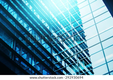 Modern Business Office Building Windows Repeating Pattern, Blue Glass Facade with Geometric Lines, Sunlight Reflecting