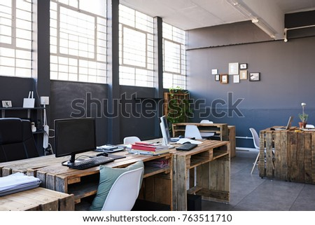Modern business office interior containing tables and chairs, computers and office supplies with no employees