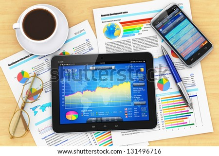 Modern business office workplace: tablet PC computer, smartphone with stock market application, documents with financial reports, graphs and charts, pen, eyeglasses and cup of coffee on office table