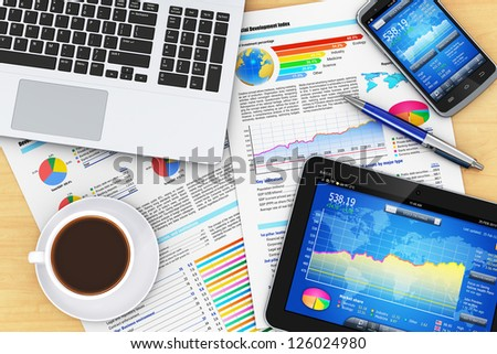 Modern business office workplace technology concept: laptop computer, tablet PC, smartphone with stock market financial application and documents with financial reports on wooden office table - stock photo