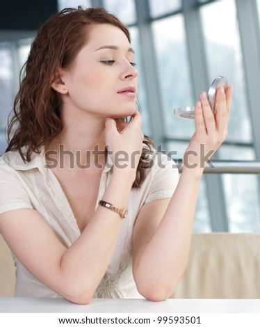 Modern business woman doing make-up at lunch time