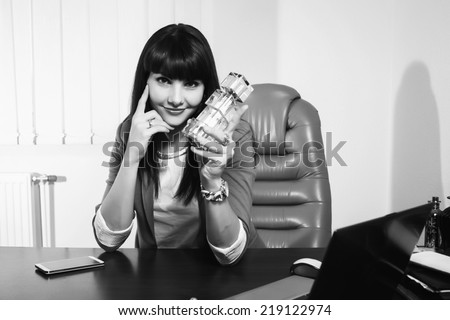 Modern business woman employee of the perfume company. Business lady sitting at a desk. Woman holding a bottle of perfume, offers its customers. Cosmetics, perfumes, sales concept of women\'s business.