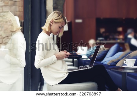 Modern business woman or successful working on smart phone and laptop computer at coffee shop interior, female student sitting in university library while using technology, internet distance work