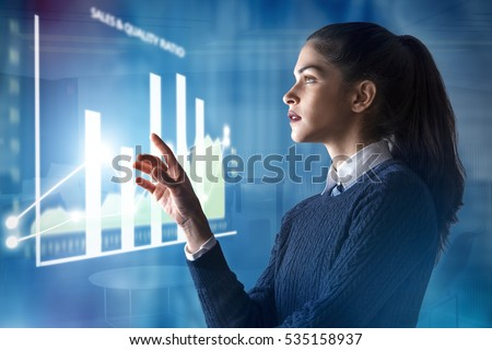 modern business woman using innovative technologies to manage her administrative work, analyzing a digital projected graph