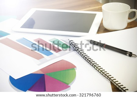 Modern business workplace  on digital tablet, mobile banking on a smartphone and some charts and graphs on a desktop.