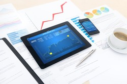 Modern business workplace with stock market data application on a digital tablet, mobile banking interface on a smartphone and some papers with charts, graphs and numbers on a desktop.