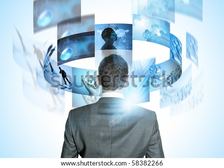 Modern Business World, A businessman looking at rotating business images. - stock photo