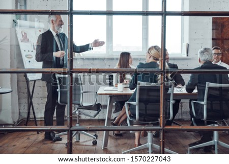 Modern businessman conducting a presentation while having staff meeting in the board room