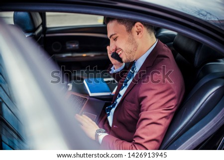 Modern businessman driving in a limo is having a phone conversation while using his lap top