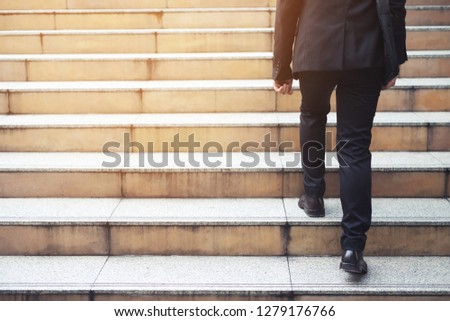 modern businessman hand holding briefcase backside working close up legs walking up the stairs in modern city. in rush hour to work in office a hurry. During the first morning of work. stairway