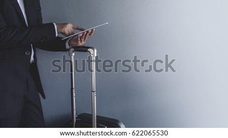 Modern Businessman wearing suit and touching a digital tablet at grey wall in the airport, Business trip concept, Side view #622065530
