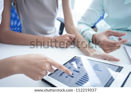 Modern businesspeople discussing the progress shown through digital graphs
