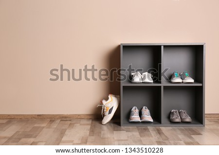 Modern cabinets with different sneakers near color wall, space for text