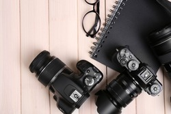 Modern cameras with glasses and notebook on wooden table, top view