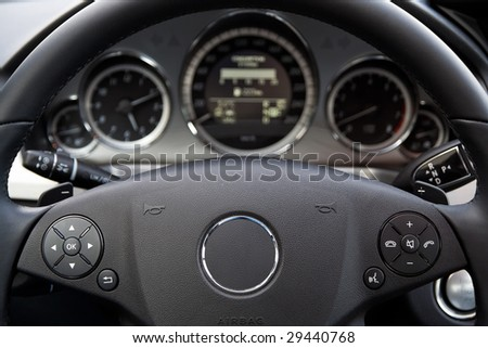 Modern car dashboard. Focus on steering wheel.