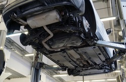 Modern car in a car service. Bottom view. The underside of the car, suspension and exhaust system elements. Car service and spare parts.