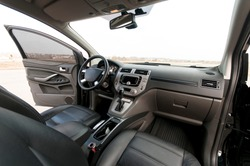 Modern car interior, black perforated leather, aluminum, details controls, leather steering wheel
