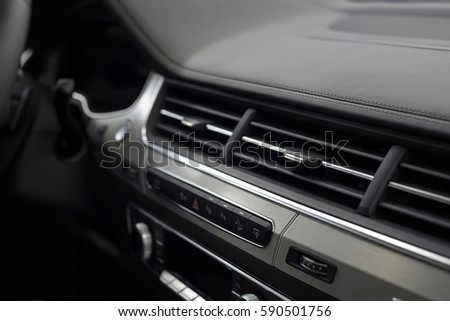 Modern car leather dashboard with control buttons. Interior detail.