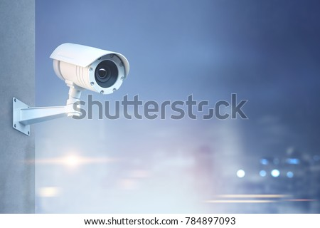 Modern CCTV camera on a wall. A blurred night cityscape background. Concept of surveillance and monitoring. Toned image double exposure mock up