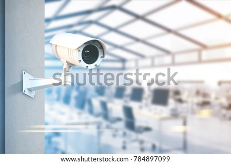 Modern CCTV camera on a wall. A blurred open space office with rows of computers background. Concept of surveillance and monitoring. Toned image double exposure mock up #784897099