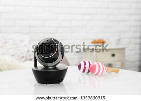 Modern CCTV security camera and rattles n table indoors. Space for text Foto stock ©