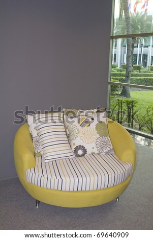 Modern chair within sparsely furnished room with brightly colored scatter cushions