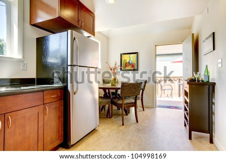 Modern cherry kitchen with steal appliances and open door.