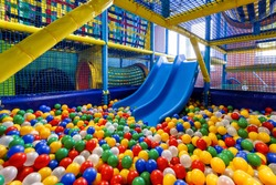Modern children playground indoor. Inside the beautiful kids playground with a slide. Panoramic view of plastic dry pool with colorful balls for playing.