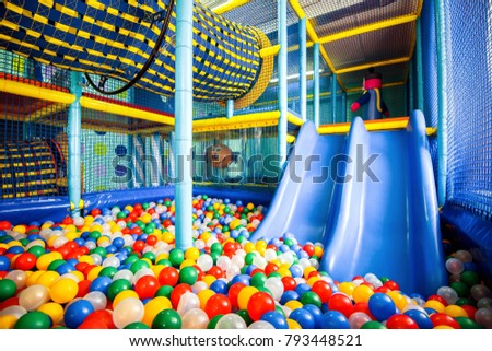 Modern children playground indoor. Inside the colorful plastic structure for active games and development of motor skills. Pool with colored balls and slide. Kids playground for gym in kindergarten.  #793448521