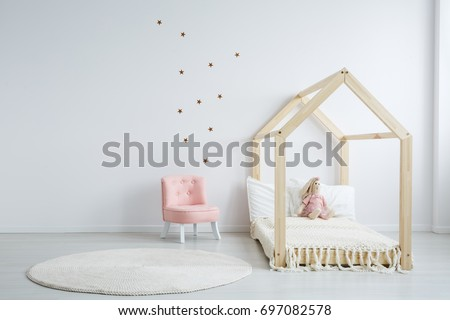 Modern children's furniture in a spacious bedroom with star stickers on the white wall, and a pastel pink comfortable chic chair next to a wooden bed #697082578