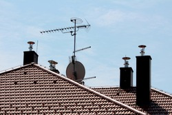 Modern chimneys with new shiny metal pipes on top surrounding tall metal pole with multiple TV antennas on top of suburban family house new roof on clear blue sky background