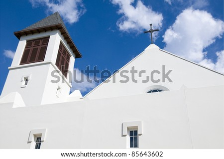 Modern christian church steeple with cross and blue sky - stock photo