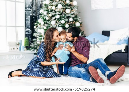 Modern Christmas Family Portrait In Home Holiday Living Room. Mother and father kissing Kid Baby waiting Santa With Present Gift Box, House Decorating By white Xmas Tree Candles Garland