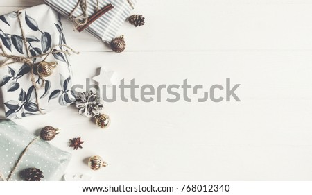 modern christmas flat lay. wrapped presents with ornaments and pine cones anise on rustic white wooden background top view, space for text. stylish gifts. seasonal greetings. happy holidays #768012340