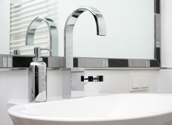Modern chrome tap, faucet, with a soap dispenser besides it