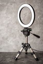 Modern circular neon led lamp for make-up artist or photographers on gray concrete background
