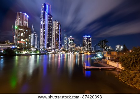 modern city at night with moving clouds and pier in foreground