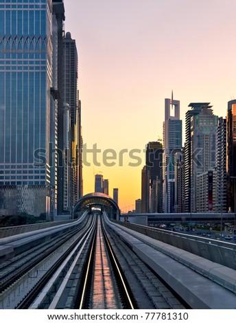 Modern city at sunset, metro overpass with rails, Dubai city in United Arab Emirates - stock photo