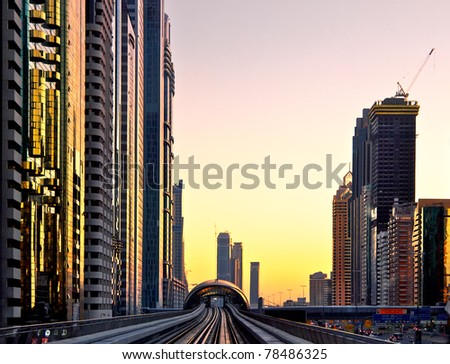 Modern city at sunset, metro overpass with rails, Dubai city in United Arab Emirates