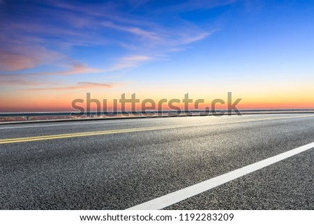 Modern city skyline and buildings with empty asphalt road at sunset #1192283209