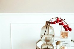 Modern classic interior design. Decorated living room. Bedside table with red berries bouquet in glass vase, book, candle in front of beige wall. Comfortable home apartment.