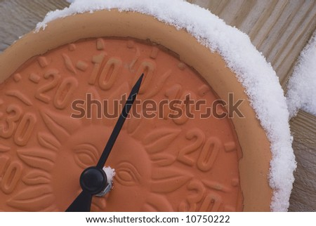 Modern clay thermometer with snow on top of it pointing at 0 degrees Celsius.